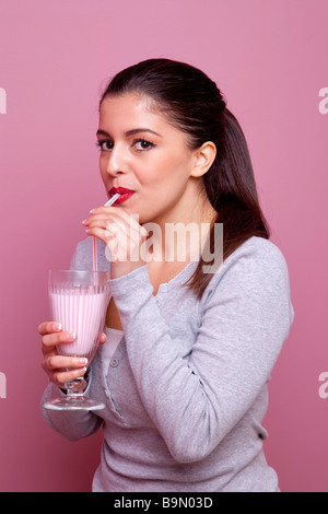 An attractive woman drinking a glass of strawberry diet milshake through a straw pink background - Stock Photo