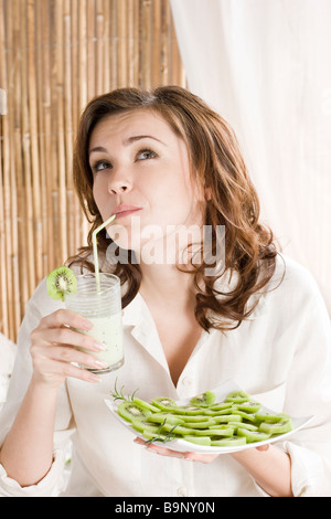 woman drinking kiwi milkshake - Stock Photo