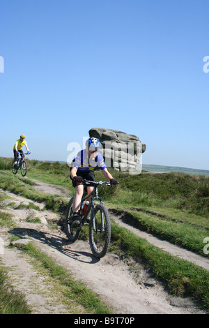 Ten year old boy mountain biking off-road on Baslow Moor in Peak District with  father following behind - Stock Photo