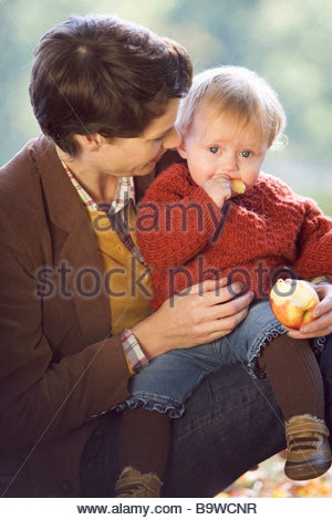 A young mother smiling at her baby eating an apple - Stock Photo