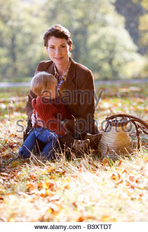A young mother sitting in the grass holding her baby - Stock Photo