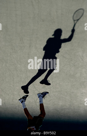 Shadow of tennis player in action - Stock Photo