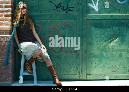 Trendy young woman sitting on stool in front of graffitied wall - Stock Photo