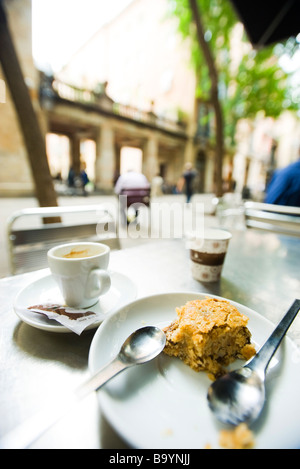 Coffee cup and half eaten pastry left on sidewalk cafe table - Stock Photo