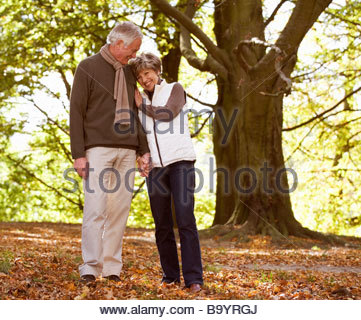 A senior couple holding hands in autumn time - Stock Photo