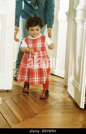 Little girl walking, mother following behind - Stock Photo