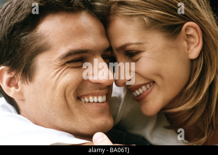 Couple touching foreheads, smiling at each other - Stock Photo