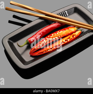 fresh red chili peppers on a plate with chopstikcs over grey reflective surface - Stockfoto
