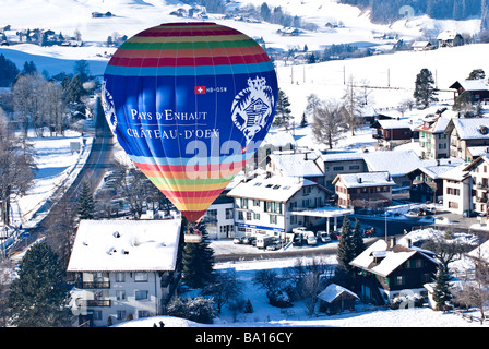 The 'Chateau d'Oex' balloon floats above the village: 2009 International Hot Air Balloon festival Chateau d'Oex - Stock Photo