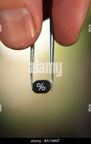 Close up of hand with tweezers holding a calculator key with the percent symbol. - Stock Photo