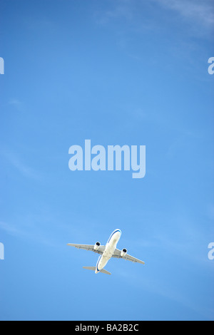 Commercial Airplane Flying Against A Blue Sky - Stock Photo