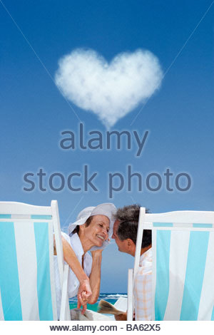 Couple in lounge chairs with heart cloud overhead - Stock Photo