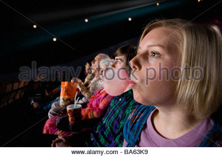 Audience in cinema, woman blowing bubble with gum, side view - Stock Photo
