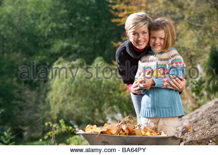 Portrait of mother and daughter holding leaves near wheelbarrow - Stock Photo