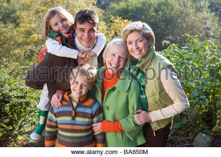 Portrait of three generation family standing by trees - Stock Photo
