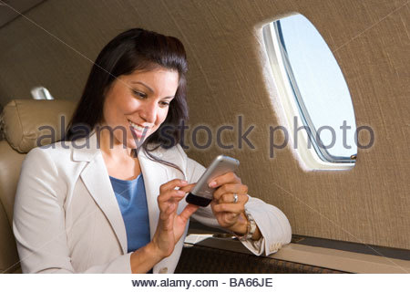 Businesswoman using electronic organiser on aeroplane, smiling, close-up - Stockfoto