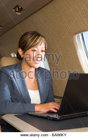 Businesswoman using laptop computer on aeroplane, smiling, close-up - Stockfoto
