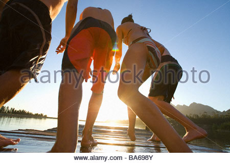 People jumping off dock into lake - Stockfoto