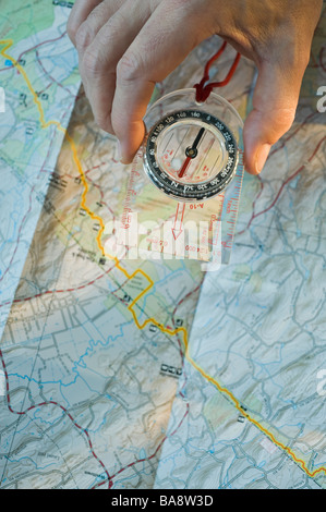 Man holding compass over map - Stock Photo