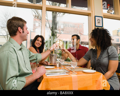 Friends toasting in restaurant - Stock Photo