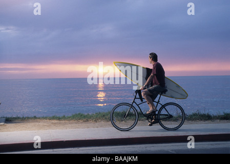 Man riding bike with surfboard in La Jolla, California. - Stock Photo