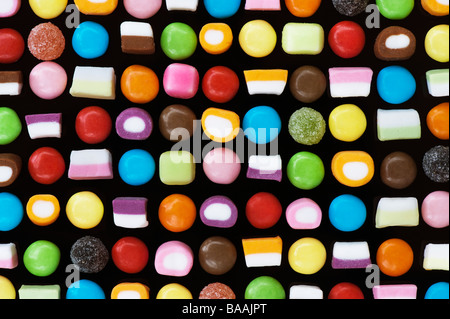 Multicoloured dolly mixtures and smarties sweets pattern on black - Stock Photo