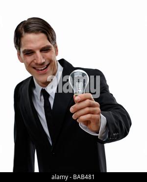 A man holding a light bulb, Sweden. - Stock Photo