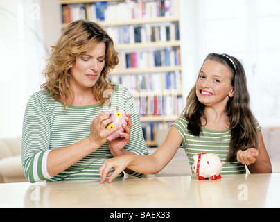 indoor, people, mother, daughter, woman, 30-35, child, girl, 5-10, 10-15, blonde, smile, smiling, joy, saving, pig, - Stock Photo