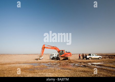 Digging for water in an old dried up lake bed caused by climate change induced drought near Dongsheng northern China - Stock Photo