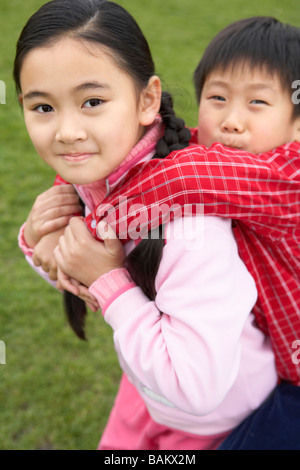 Girl Giving Boy A Piggy Back Ride - Stock Photo