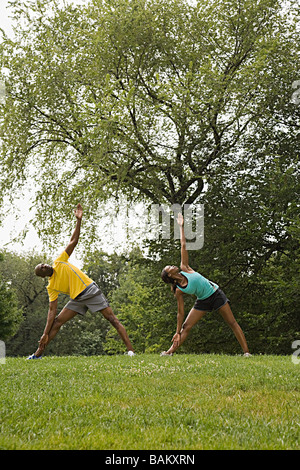 People doing yoga in park - Stock Photo