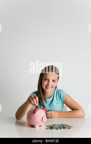 Girl with piggy bank and coins - Stock Photo