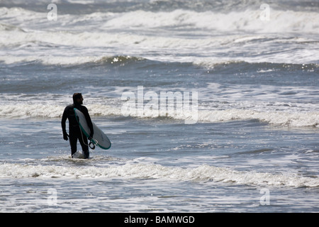 Surfers in silhouette on a beach in Oregon - Stock Photo