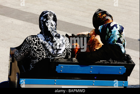 Three Turkish woman with scarf, sitting on a carriage wagon. Miniaturk, Istanbul, Turkey, April 2009 - Stock Photo