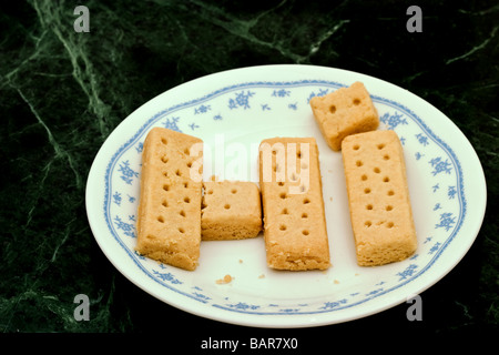 Shortbread cookie fingers on a white decorated plate spelling the work HI. - Stock Photo