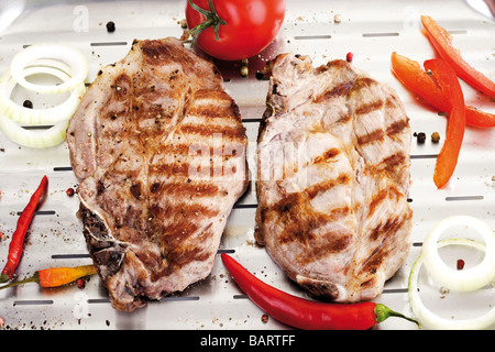 Grilled Pork chop on aluminium grill pan - Stock Photo