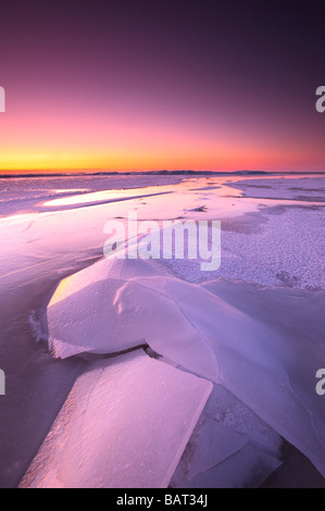 A frozen lake glows in morning twilight - Stock Photo