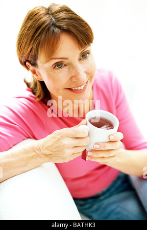 Herbal tea. Woman holdinga cup of herbal tea. Herbal tea is an infusion ofherbs in boiling water. - Stockfoto