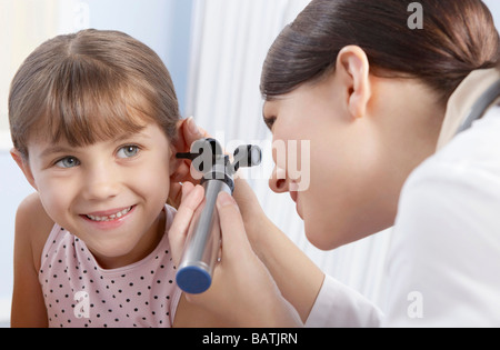 Ear examination. Otoscope being used by a general practice doctor to examine a six-year-old girl's ear. - Stockfoto