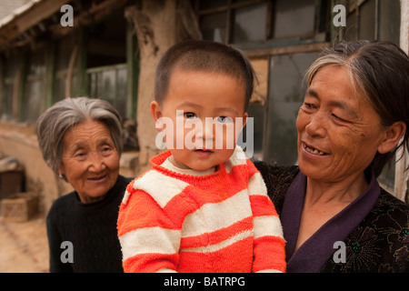 Changchun, Jilin Province, China.  A young boy in the arms of his mother outside their home with his grandmother - Stock Photo