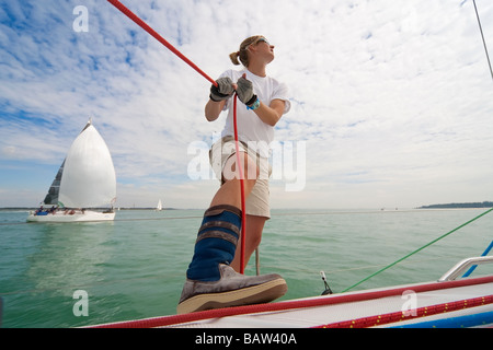 A woman crew member on board a racing yacht with a competing boat in the background - Stockfoto