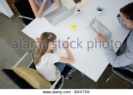 Father reading newspaper at table while daughter draws - Stockfoto