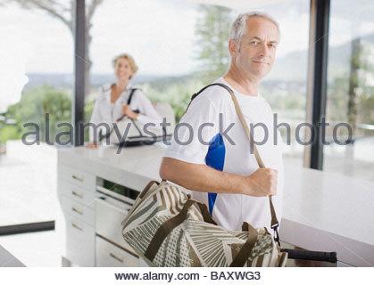 Man carrying tennis racquet in gym bag - Stock Photo