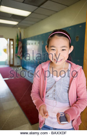 Girl listening to mp3 player in school hallway - Stock Photo