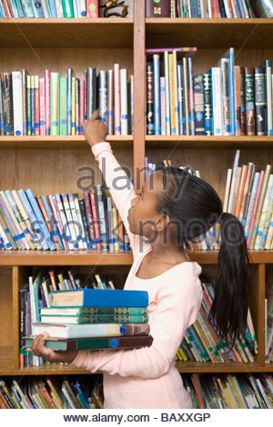 Girl taking books from school library - Stock Photo
