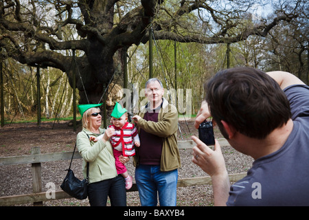 Tourists posing in 'Robin Hood' hats for a family photograph at the Major Oak, Sherwood Forest, Nottinghamshire. - Stock Photo