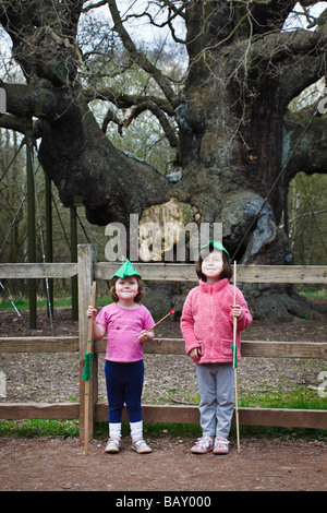 Children wearing 'Robin Hood' hats at The major Oak in Sherwood Forest, Nottinghamshire. - Stock Photo