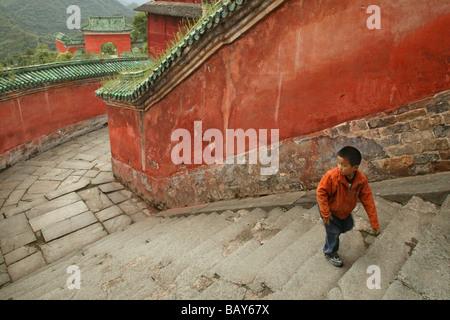 Child climbing the steps, red walls of the Purple Cloud Temple, Zi Xiao Gong, Mount Wudang, Wudang Shan, Taoist - Stock Photo