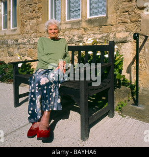 Elderly woman sitting outside her house. - Stock Photo