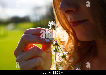 woman holding a daisy chain in the sunshine. - Stock Photo